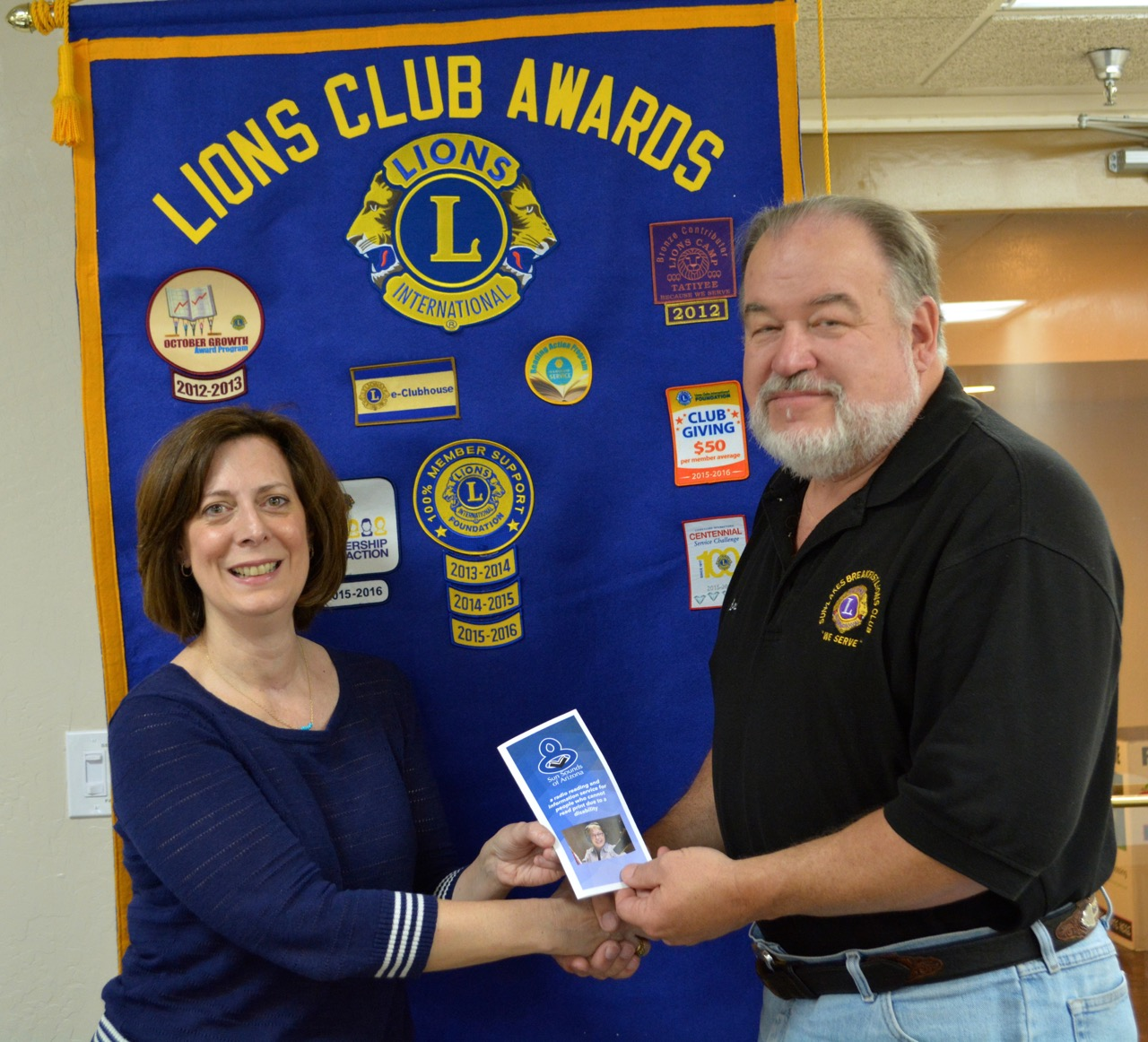 Andrea Pasquale hands Lion President Brian Curry a brochure in front of a blue Lion Flag
