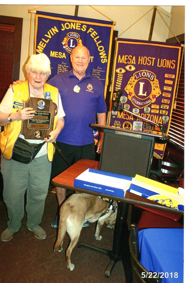 Connie receives award fromPast Council Chair Lion Jim Sterenberg in front of a purple Lion's banner that Reads Melvin Jones Fellow Mesa Host.  Connie's dog Amity is looking under a table.