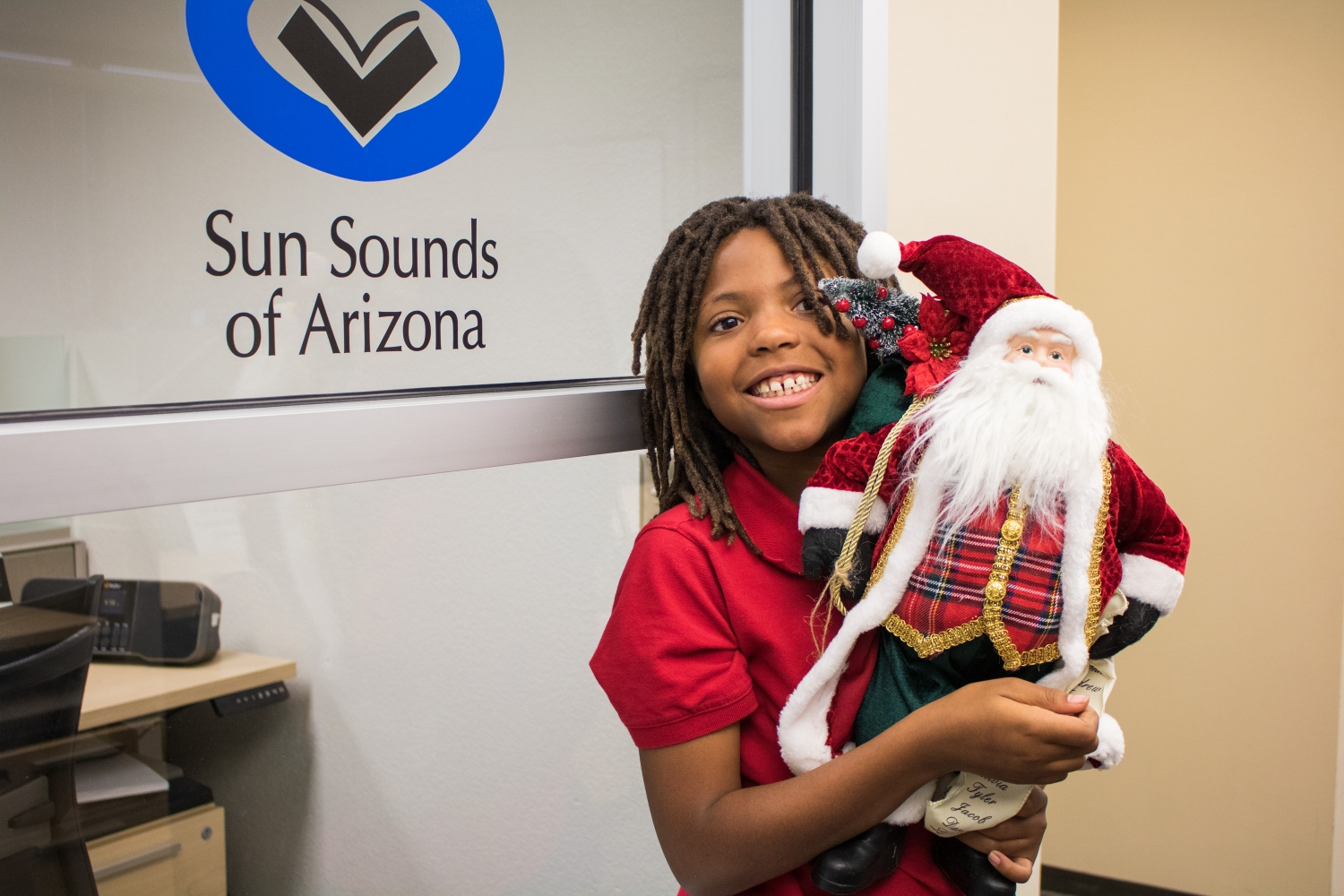 Little girl in red shirt holds a Santa Clause doll