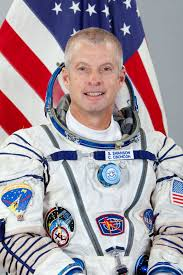Photo of Steve Swanson in his astronaut uniform in front of a draped American flag