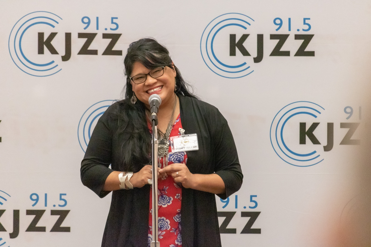woman red floral top and black jacket,  black hair and glasses smiling in front of a microphone