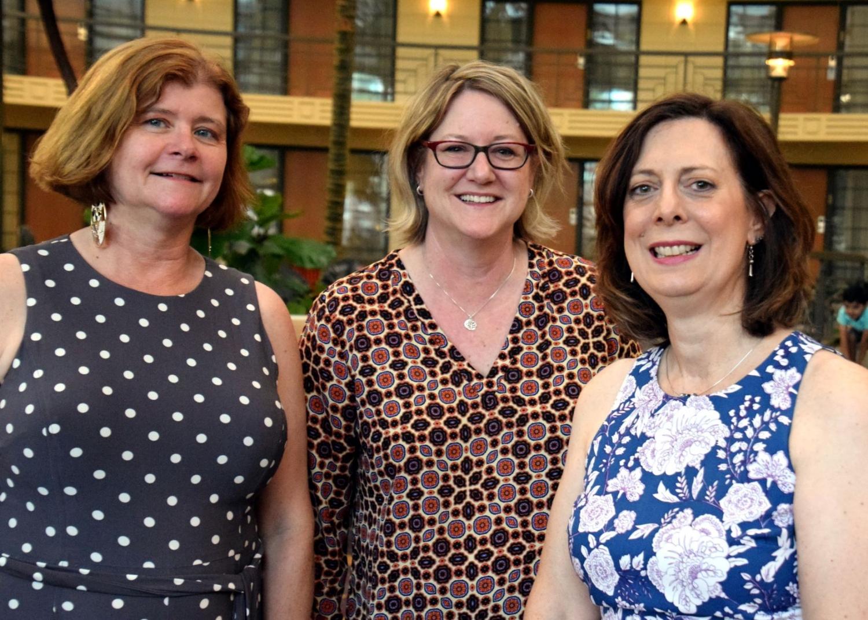 Three women standing smiling