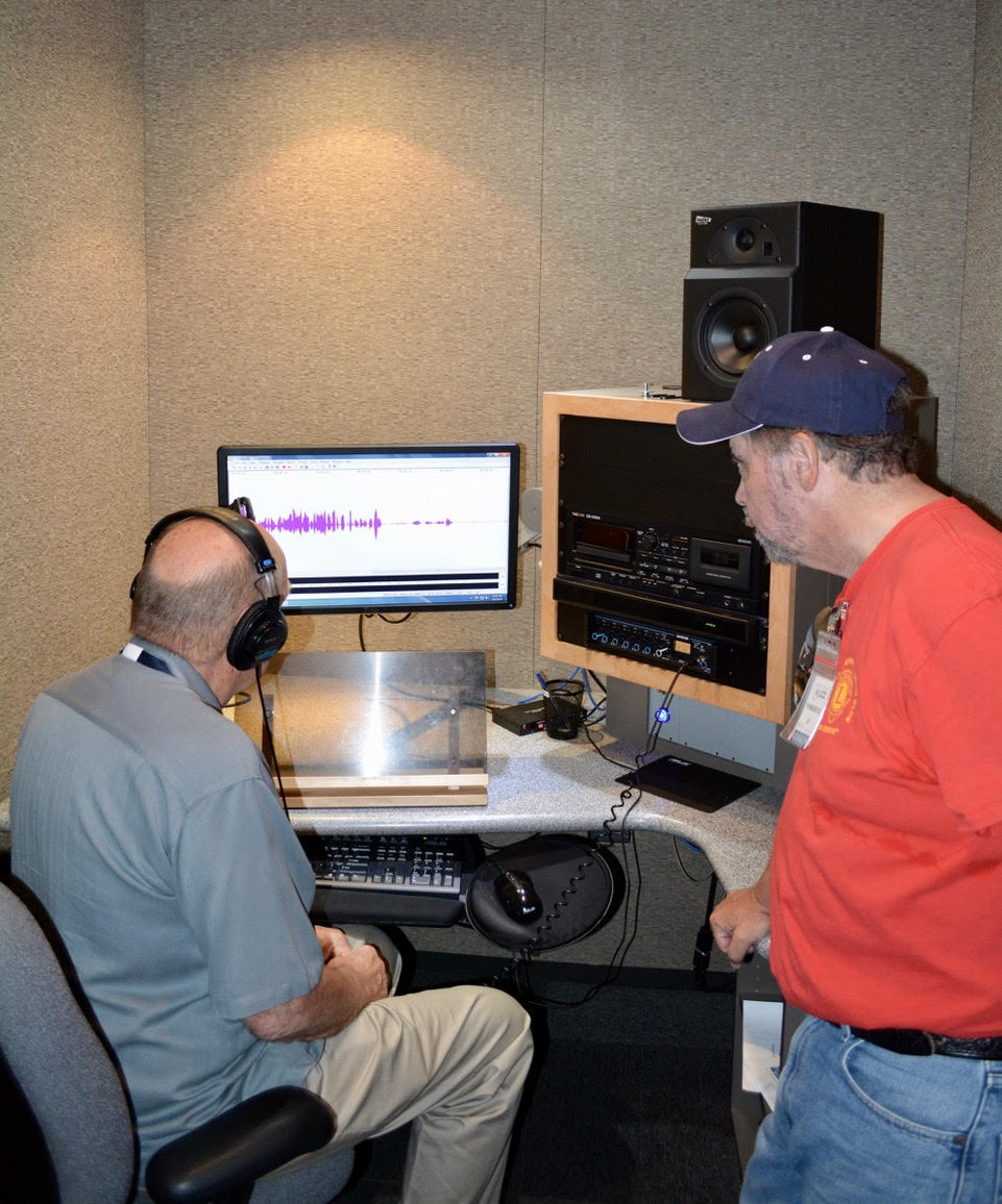 Volunteer Mike Ameigh shows Lion Rich Iovino how to record a program