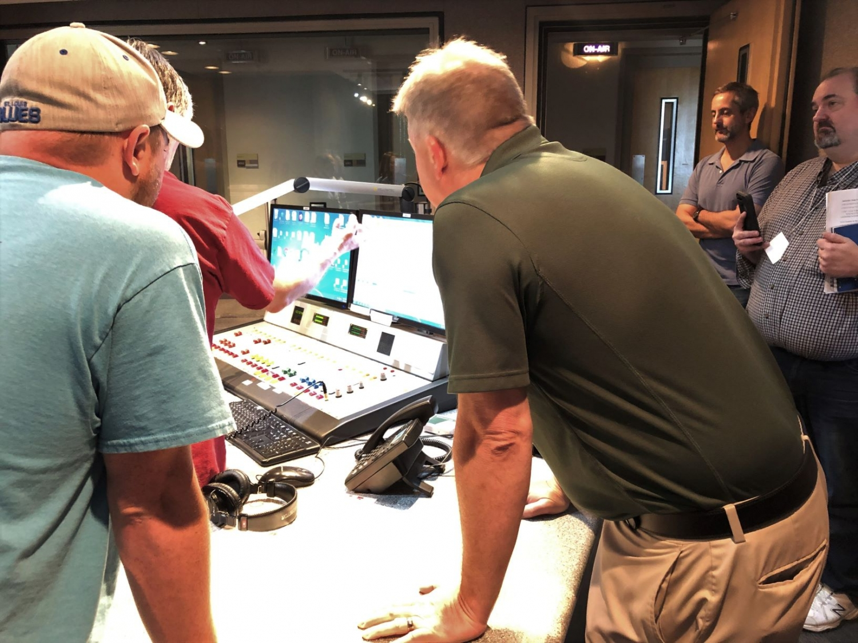Men look at studio control board, two men lean in to look at board