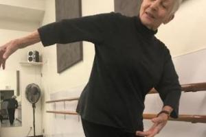 A woman turns her body at a ballet studio